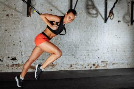Trx concept. lady exercising her muscles with help of suspension trainer sling