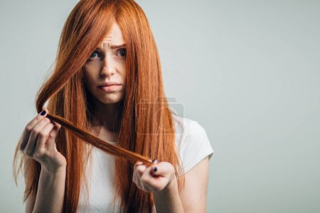 Sad redhead girl holding her damaged hair looking at camera.