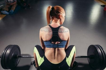 Rear view of sportswoman while lifting barbell
