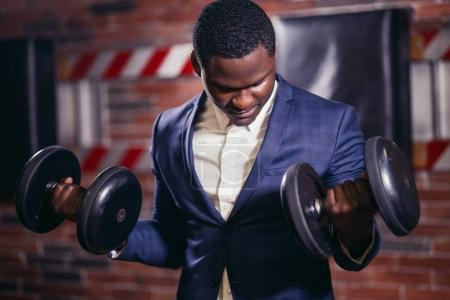 African fitness model exercising with heavy dumbbells.