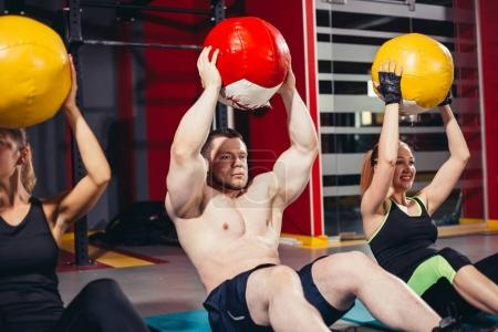 People exercising with pilates ball at gym.