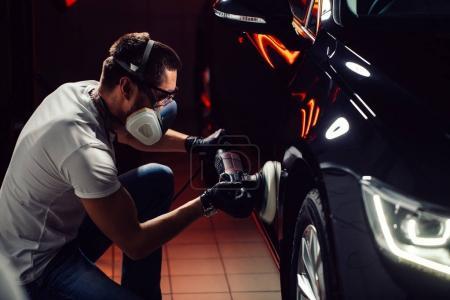 Photo pour Détailler de voiture - les mains avec une polisseuse orbitale en atelier de réparation automobile. Mise au point sélective. - image libre de droit