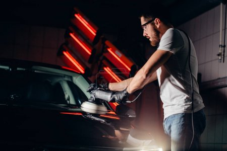 Car polish wax. worker hands holding a polisher