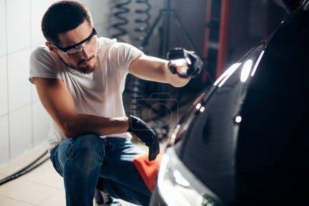 man checks polishing with a torch