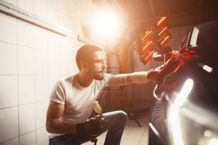 man cleaning car with microfiber cloth, car detailing or valeting concept