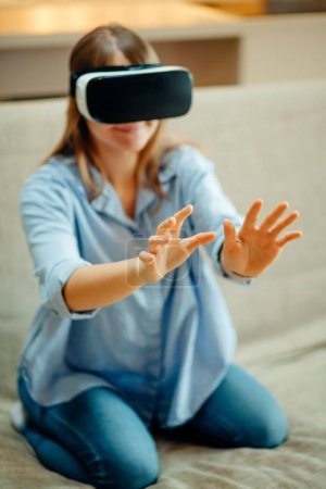 woman adjusting her VR headset and smiling while sitting on the carpet at home
