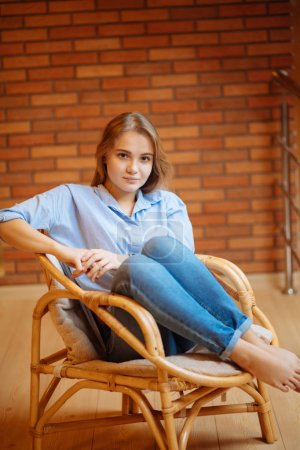 Photo for Beautiful young woman relaxing in big comfortable chair - Royalty Free Image