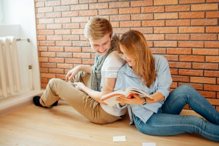 Couple students sitting outside classroom and studying together