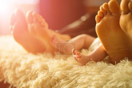 family laying on bed, their feets on focus. Mother, father and newborn baby son