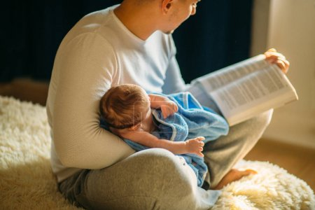 Young father and reading book to little baby