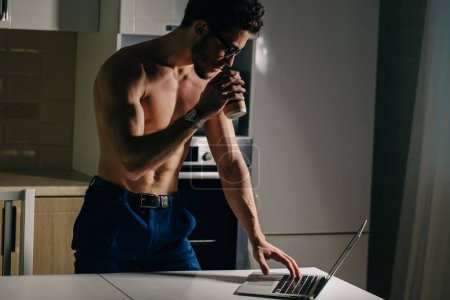 Fit Man Using Laptop and drink coffee at morning