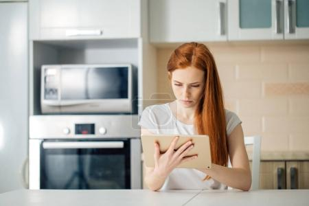 female entrepreneur thinking while working at table in her kitchen at home