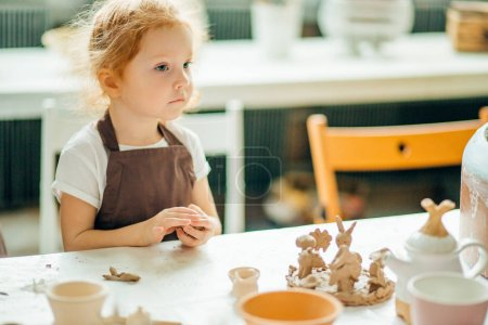 girl looking sideway near clay toys at table