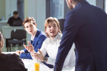 smiling male boss talking to business group