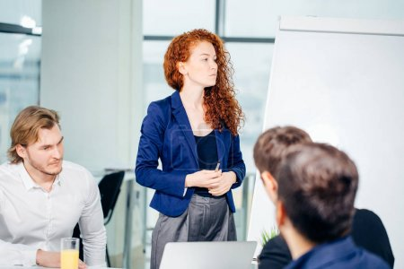 Business woman giving presentation to colleagues in office