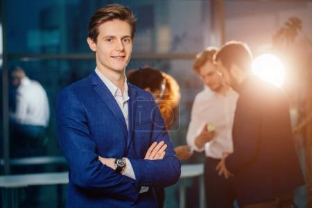 small business owner standing with crossed arms with employee in background