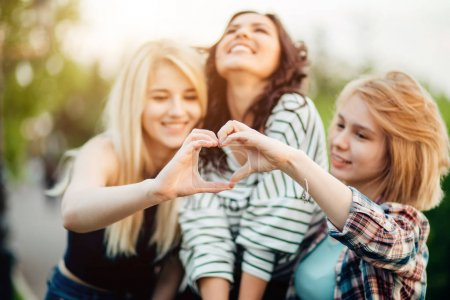 three female friends making heart shape from hand