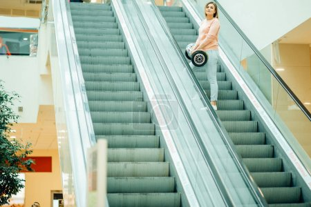 girl with hoverboard rides on the escalator