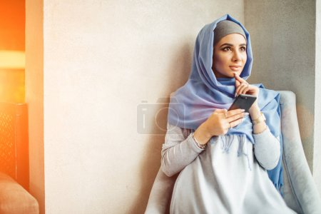 muslim young woman use smart phone in cafe