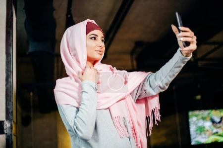 Portrait of a young attractive woman in hijab making selfie photo on smartphone
