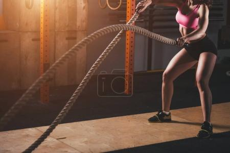 woman working out in training gym doing cross fit exercise with battle ropes