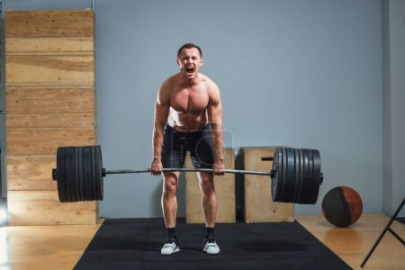 Photo for Muscular fitness man doing deadlift barbell in modern fitness center.Functional training - Royalty Free Image