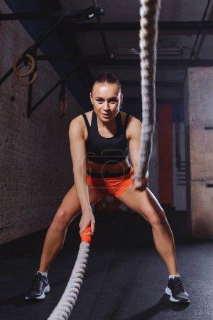 Photo pour Bataille des cordes session. Sportive fit et tonique, travail avec cordes de bataille - image libre de droit