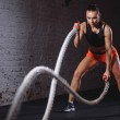 Woman training with battle rope in cross fit gym...