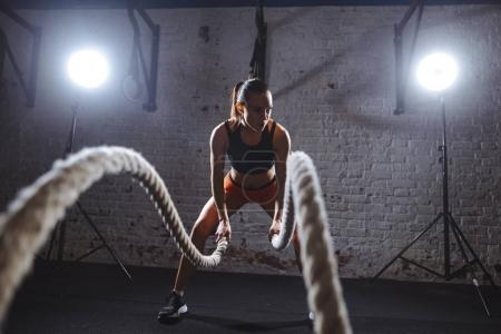 Young woman working out with battle ropes in cross fit gym