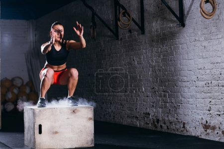 woman jumping box. Fitness woman doing box jump workout at cross fit gym.