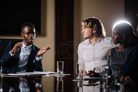 black male boss talking to business team in conference room