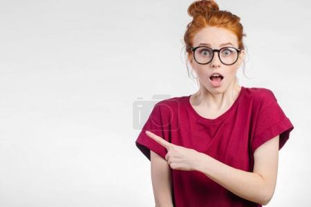 Surprised girl showing empty copy space with her finger white background