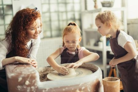 mother and two redhead daughters made clay cup with pottery wheel