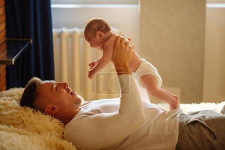 father playing with adorable baby in bedroom