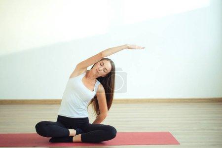 Young slim girl makes aerobics exercise sitting in lotus pose on mat