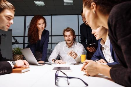 business, technology and office concept - smiling boss talking to business team