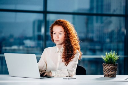 redhead businesswoman sitting at bright modern work station and typing on laptop