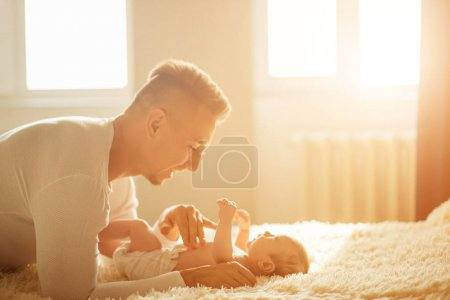 Father lying on bed and holds his baby