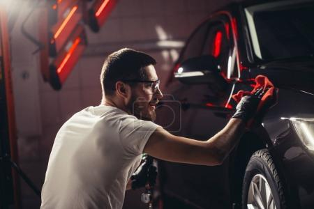Car detailing - the man holds the microfiber in hand and polishes the car