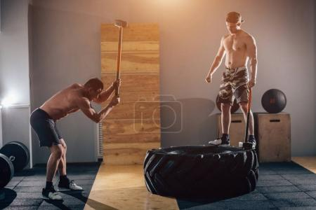 Sledgehammer Tire Hits men workout at gym with hammer and tractor tire