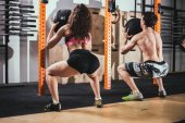 fit, sport and exercising concept - people with medicine balls training in gym