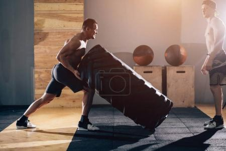 trainer standing on tire and scream at a man exercising with a tire.