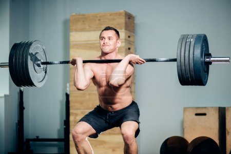 Photo for Athlete wearing black shorts lifting big barbell - Royalty Free Image
