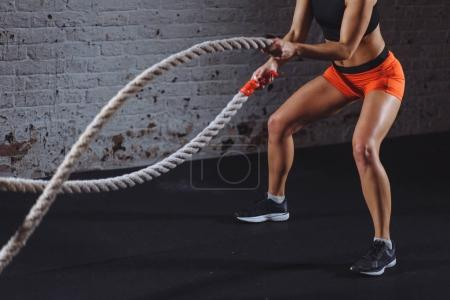 Powerful woman do workout with battle ropes in gym