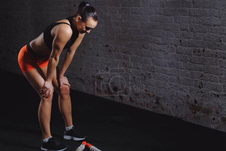 sportswoman standing at gym after battle rope workout