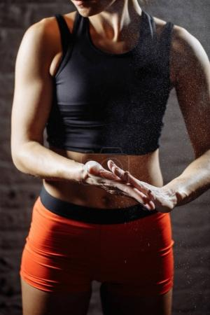 female athlete clapping hands with chalk powder before strength training