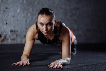beautiful woman in sportswear doing plank while trainnig at cross fit gym