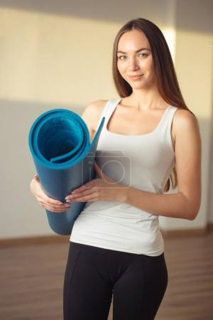 woman with yoga mat is ready for fitness