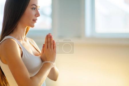 Photo pour Femme pratiquant le yoga, tenant les paumes ensemble dans namaste mudra, détendu et paisible . - image libre de droit