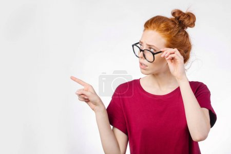 redhead woman in glasses pointing finger away at copyspace on white background
